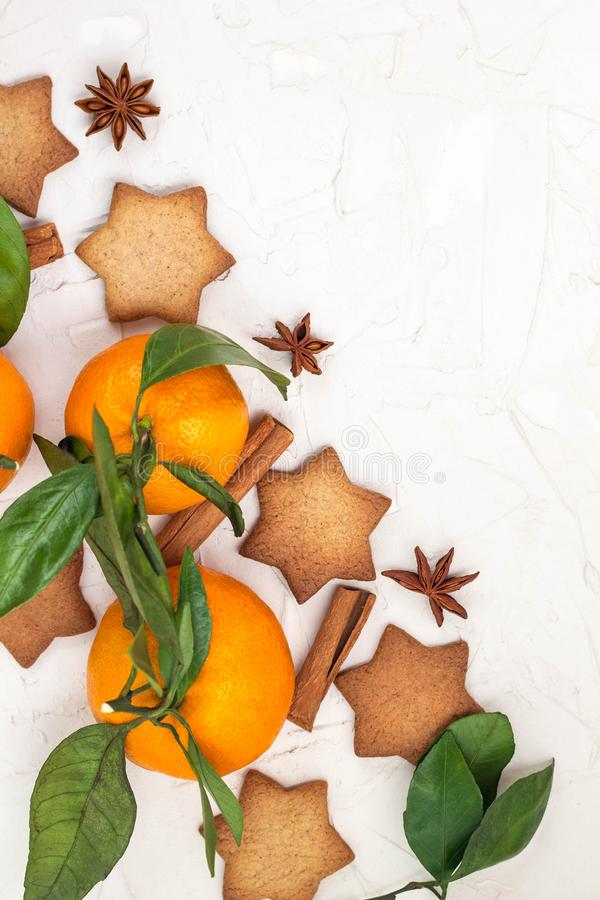 Border of Christmas star cookies with spices and mandarin on white background with copyspace. Top view stock photos