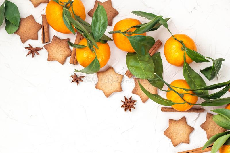 Border of Christmas star cookies with spices and mandarin on white background with copyspace. Top view stock images