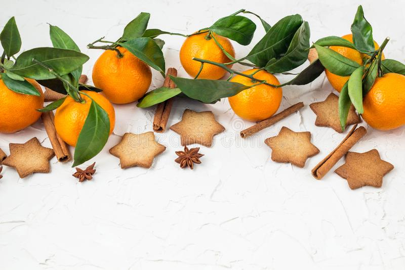 Border of Christmas star cookies with spices and mandarin on white background with copyspace. Top view royalty free stock photos
