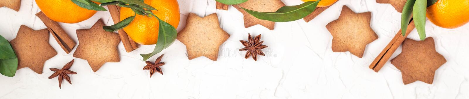 Border of Christmas star cookies with spices and mandarin on white background with copyspace royalty free stock photography