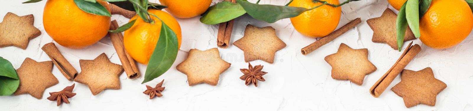 Border of Christmas star cookies with spices and mandarin on white background with copyspace. Top view, gingerbread, food, cinnamon, holiday, decoration royalty free stock images