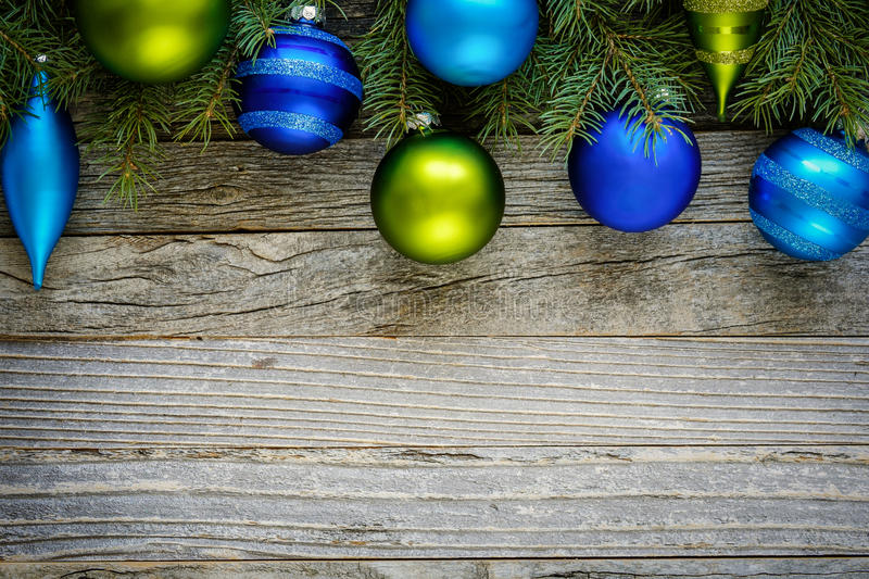Border of Christmas Tree Branches with Ornaments. Border of Christmas fir tree branches with blue and green ornaments on an old wooden board, copy space for text stock photography