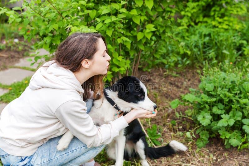 Border collie lindo huging sonriente del perro de perrito del abarcamiento atractivo joven de la mujer en fondo al aire libre del imagen de archivo