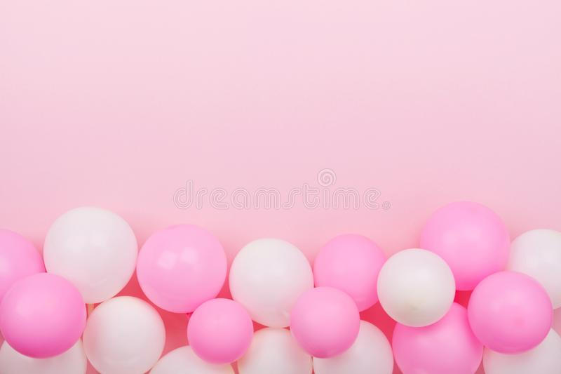 Border from colorful balloons for birthday on pastel pink table top view. Flat lay style. stock photography