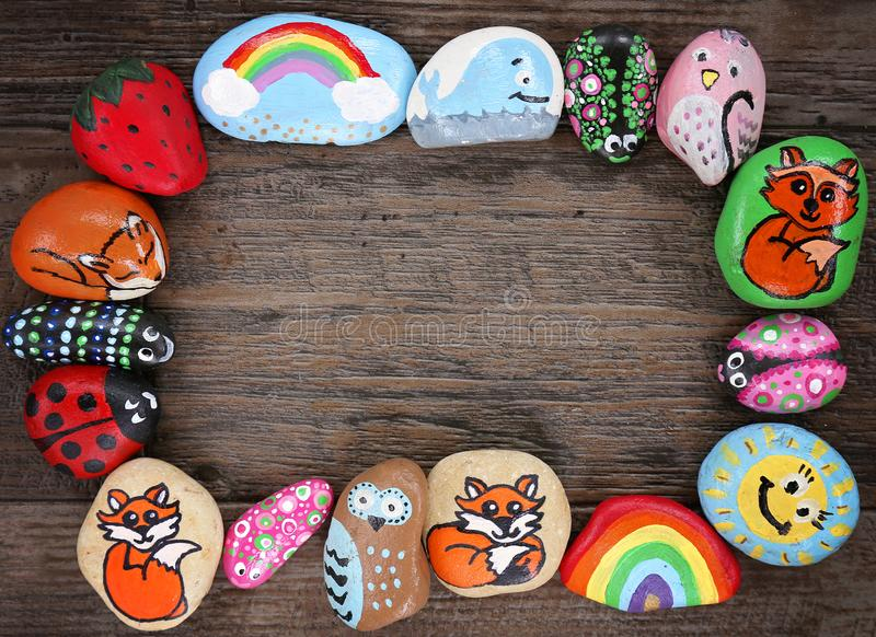 Border of Colorful Cartoon Hand Painted Animal Rocks on Wood Background. A colection of happy, colorful hand painted cartoon animal rocks are framing a wood stock photo