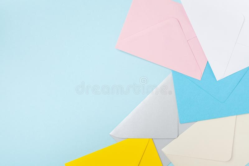 Border from colorful envelopes on blue table top view. Mockup for business mail, blogging and office correspondence. Flat lay. stock photo