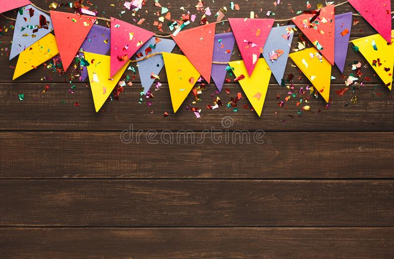 Colorful flags garland on wooden background royalty free stock photos