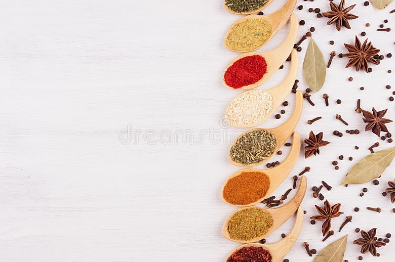 Border of colorful powdered spices in bamboo spoons and scattered anise star, clove, bay leaves, copy space, closeup. Border of colorful powdered spices in stock photos