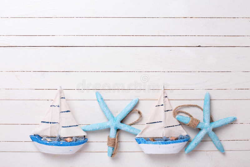 Border from decorative sailing boats and marine items on wooden stock image
