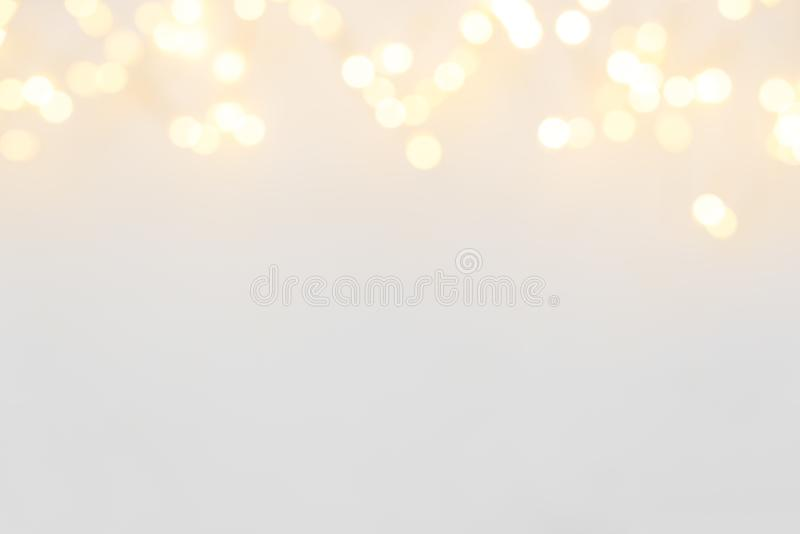 Border of defocused Christmas lights on white wooden background. Christmas and New Year holidays celebration concept royalty free stock photography