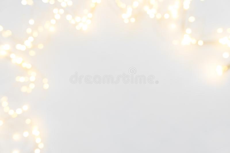 Border of defocused Christmas lights on white wooden background. Christmas and New Year holidays celebration concept royalty free stock image