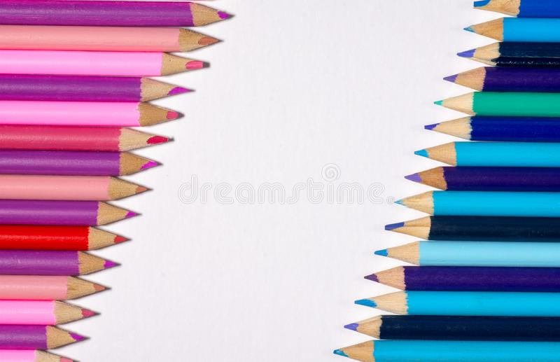 Border / edge of colored pencils with blue/purple on one side and pink/purple on the opposite with white space in-between. royalty free stock images