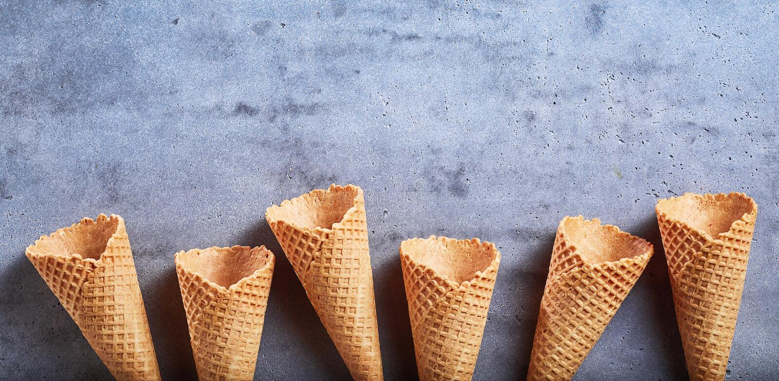 Border of empty ice cream sugar cones on slate stock photography