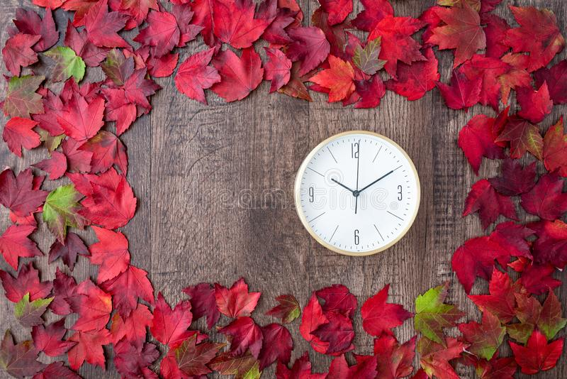 Border of fall color in red, green, yellow, and orange maple leaves on a rustic wood background, with round white analog clock stock photo