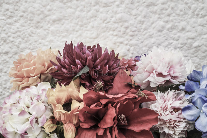 Border with flowers against white wall. Border with artificial flowers against white wall with copy space stock photos