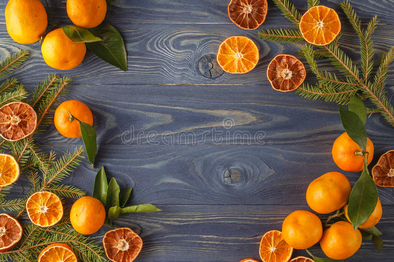 Border, frame from Christmas tree fir branches, dried orange fruit slice on old wooden desk table background. Big copyspace for h. Oliday congratulations stock images