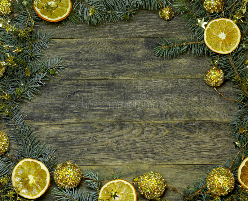 Border, frame from Christmas tree fir branches, gold pine cones. Border, frame from Christmas tree fir branches, gold ball garland decorations, dried orange stock photos