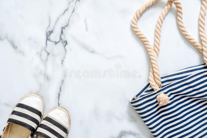Border frame of striped sandals and summer bag on marble background. Flat lay composition, above view. Concept of Summer holiday,. Vacation, sea resort, journey stock photo