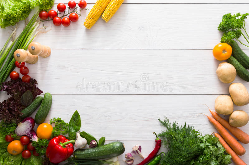 Border of fresh vegetables on white wood background with copy space. Border of fresh organic vegetables on white wood background. Healthy natural food on table stock image