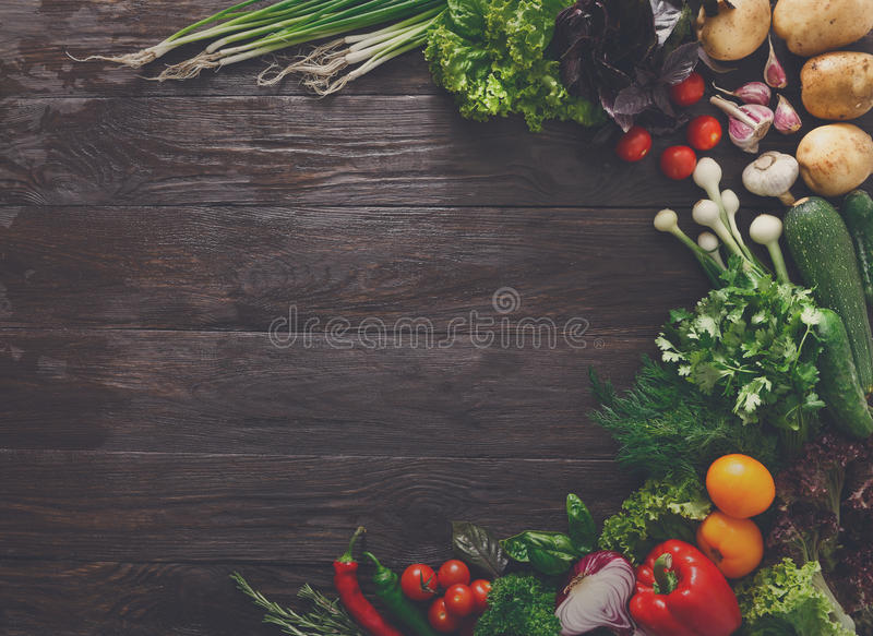 Border of fresh vegetables on wooden background with copy space. Border of fresh organic vegetables and greens on wood background. Healthy natural food on rustic royalty free stock photos