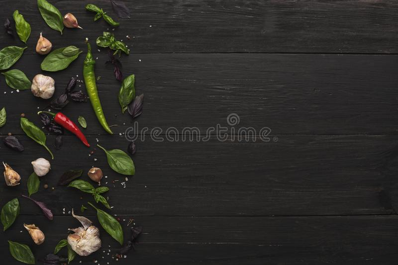 Border of fresh vegetables on wooden background. Healthy natural food on rustic wooden table. Garlic, chilli, bazil and herbs, top view stock images
