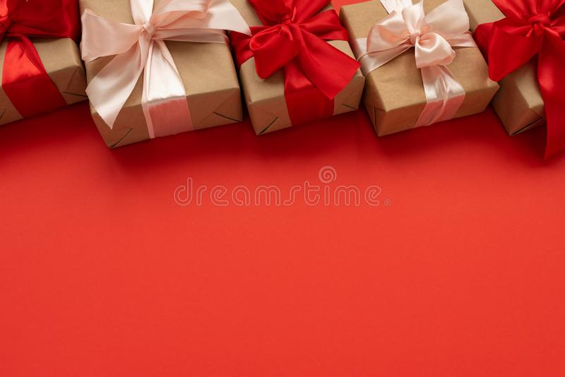 Border from gift boxes wrapped brown craft paper and red and pink ribbon on red background. Valentines day or Christmas royalty free stock image