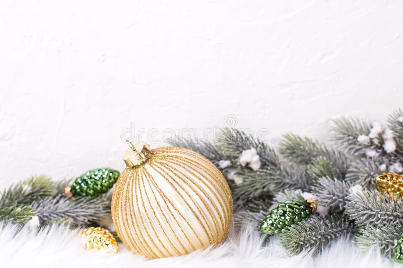 Border from gold ball and golden and green pine cones and branches fir tree near by white textured wall. Decorative christmas composition. Selective focus royalty free stock photos
