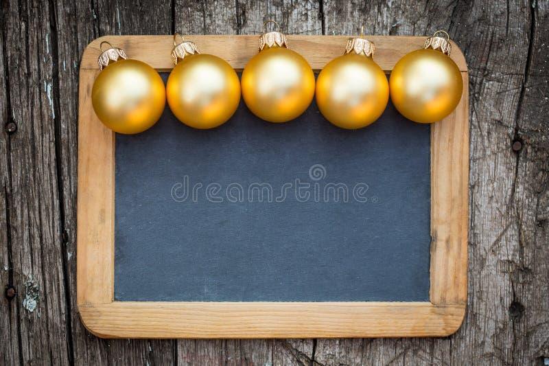 Border of gold Christmas balls. On vintage wooden blackboard blank stock photos