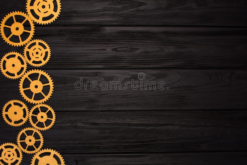 Border of gold gears on a black wooden background. View from above stock image