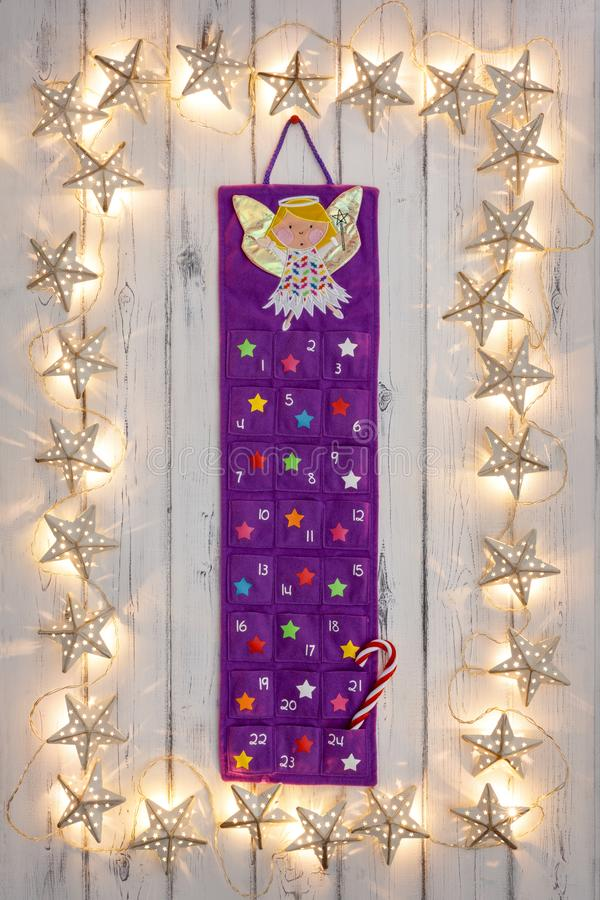 A border of golden star christmas lights, with a advent calander, on a destressed woodern background. A border of golden star christmas lights, with a advent stock photo
