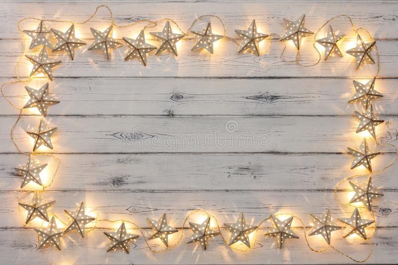 A border of golden star christmas lights, on a destressed woodern background stock photo