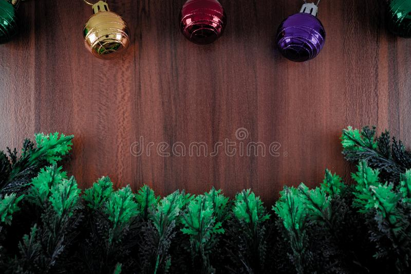 Border made from plastic cypress leaves and christmas ornament ball with wooden background. Border made from green plastic cypress leaves and christmas ornament stock image