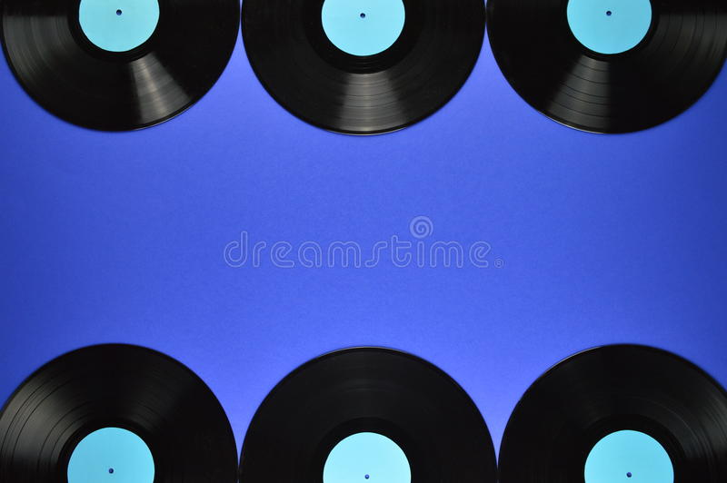 Border of old black vinyl records on blue background. Border out of old black vinyl records with blank cyan labels on blue background royalty free stock photo