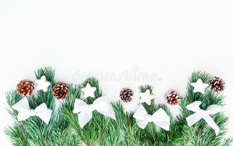 Border out of Fir Tree Twigs with Christmas Decoration. Border out of natural fir tree twigs with silver white bows, pine cones and cinnamon star cookies ( royalty free stock images