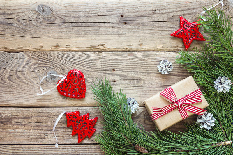Border from the pine branches, Christmas decorations and gift bo. X on an old wooden table. Holidays Christmas background. Space for text or design. Top view royalty free stock image