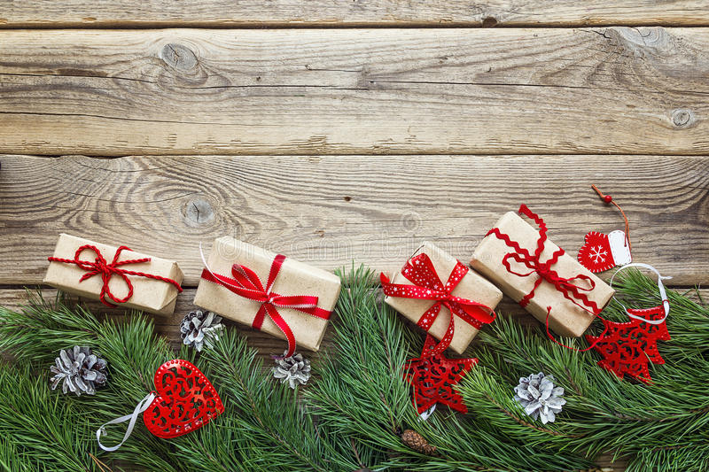 Border from the pine branches, Christmas decorations and gift bo. Xes on an old wooden table. Holidays Christmas background. Space for text or design. Top view stock image