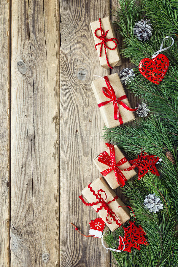 Border from the pine branches, Christmas decorations and gift boxes on an old wooden table. Holidays Christmas background. Space. For text or design. Top view royalty free stock photography