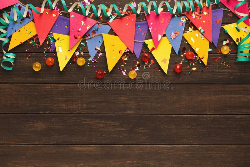 Colorful flags garland on wooden background royalty free stock photography