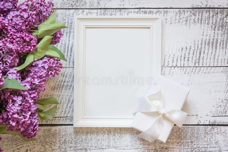 Border of purple lilac flowers and white frame for text and invitation. View from above. Border of purple lilac flowers and white frame for text and invitation stock photos