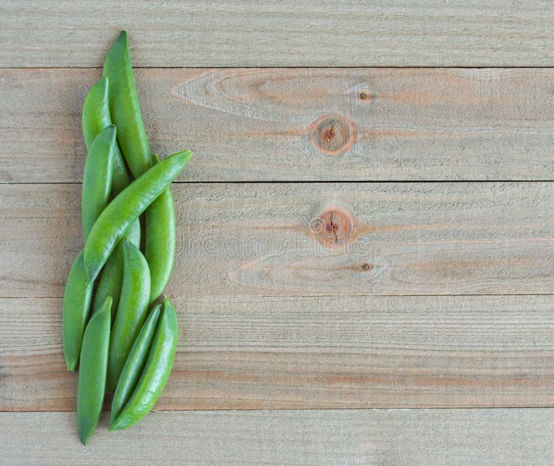 Border of ripe sugar snap peas on a wooden background stock photos