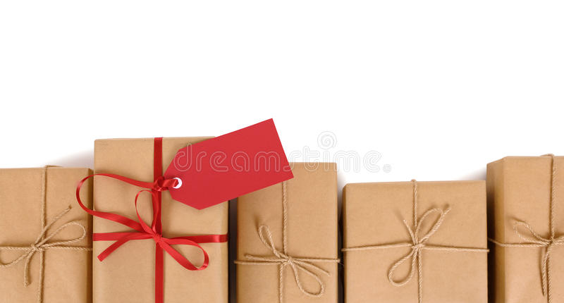 Border row of several brown paper parcels, one unique with red gift tag or label. Border of brown paper parcels, one unique with red ribbon bow and gift tag or stock photos