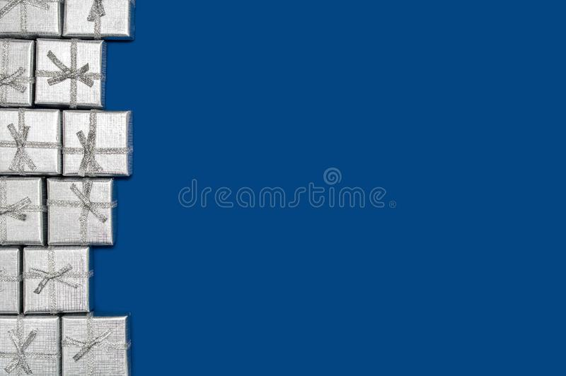 Border of silver shiny gifts on blue background. New Year`s and Christmas decor royalty free stock images