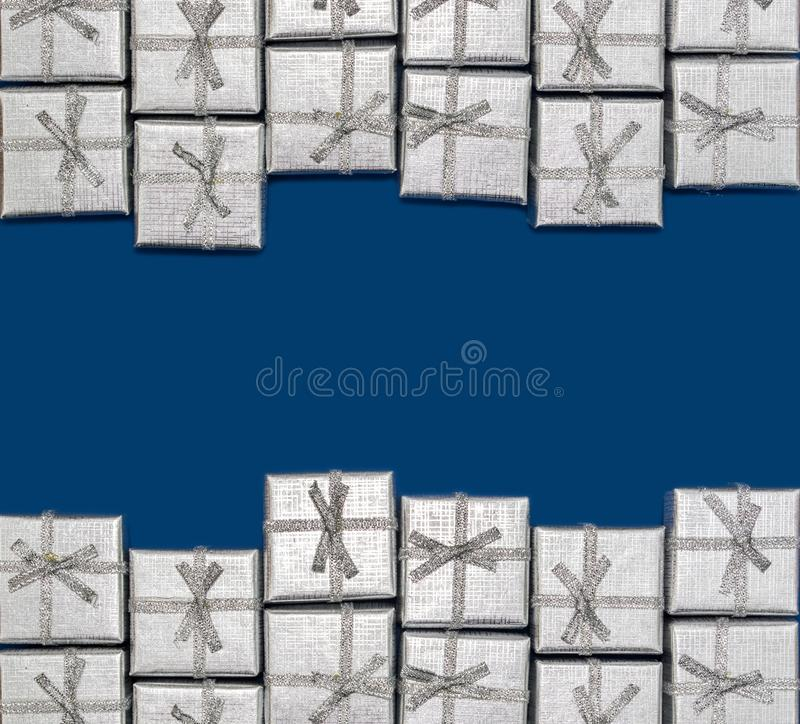 Border of silver shiny gifts on blue background. New Year`s and Christmas decor royalty free stock photography