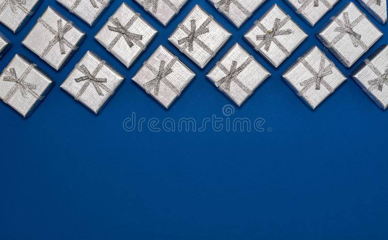 Border of silver shiny gifts on blue background. New Year`s and Christmas decorations. Group of bright gift boxes. View from above royalty free stock photography