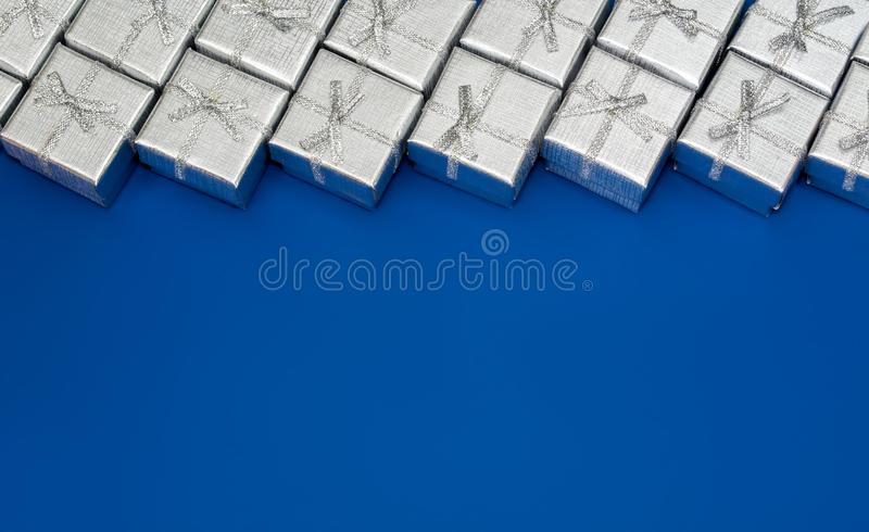 Border of silver shiny gifts on blue background. New Year`s decorations stock image