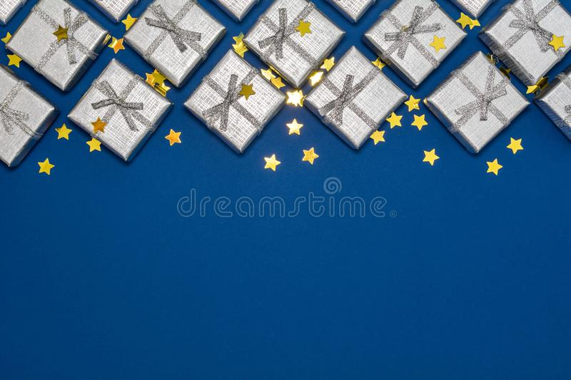 Border of silver shiny gifts and golden stars on blue background royalty free stock images
