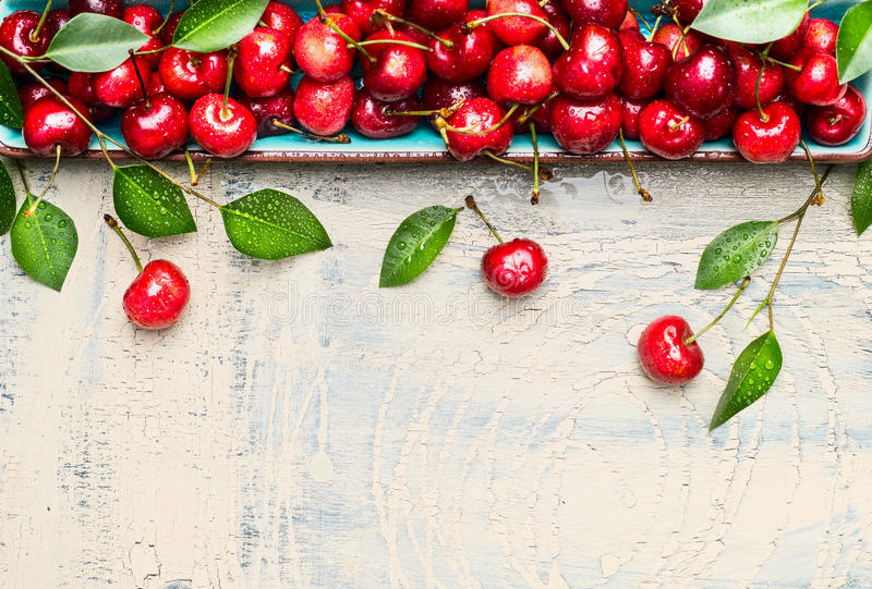 Border of sweet cherries with green leaves on light wooden background, top view, place for text stock photography