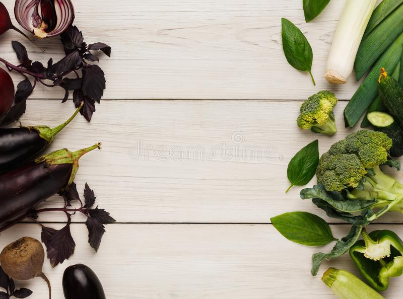 Border of various green and violet vegetables on white wood. Green and violet fresh vegetables border on white wood top view. Harvest background with cucumber royalty free stock images