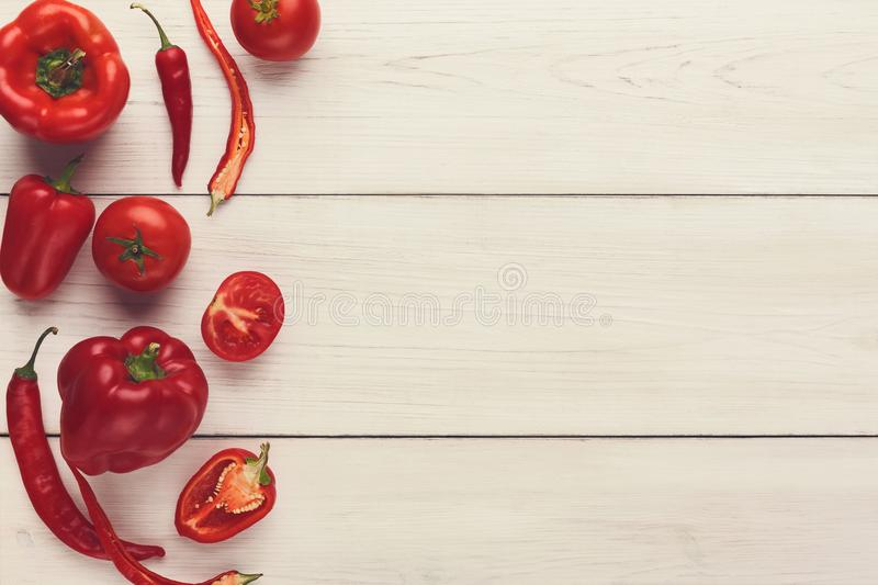 Border of various red vegetables on white wood. Red fresh vegetables border on white wood top view. Harvest background with tomatoes and peppers. Organic cooking stock image