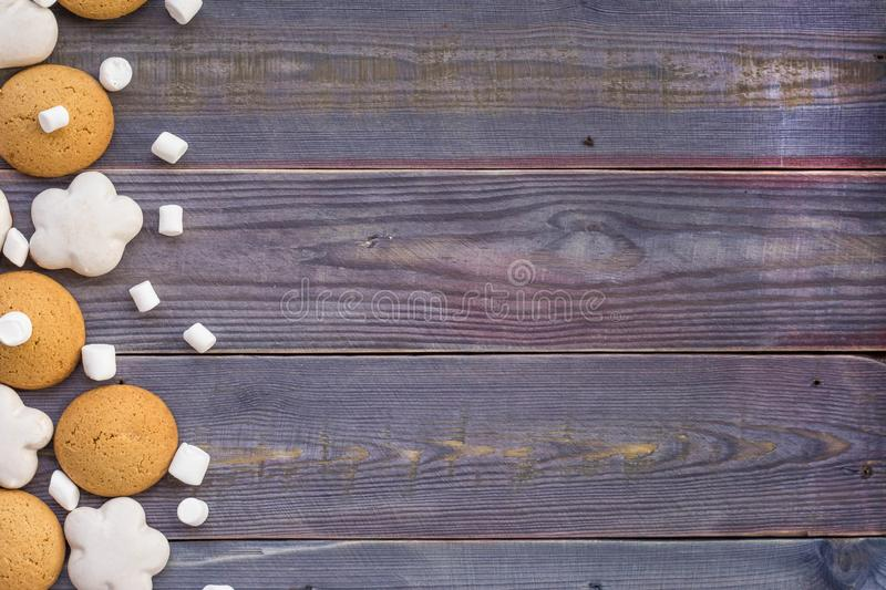 Border of white and brown gingerbread with marshmallows on wooden background.  stock photo